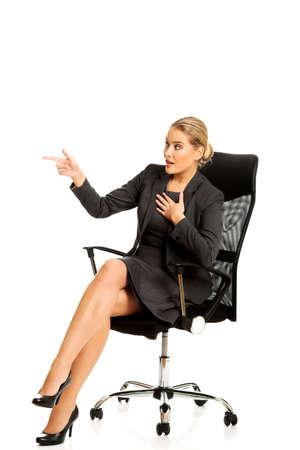 Donna di affari che si siede su una sedia e che mostra spazio vuoto