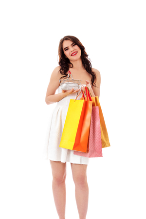 Young woman holding small empty shopping basket and shopping bags Stock Photo