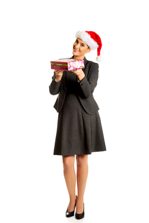 Woman weating Santa hat and holding a present Фото со стока - 122945859