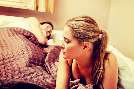 Unhappy woman lying in bed stressed when her husband sleeping Standard-Bild