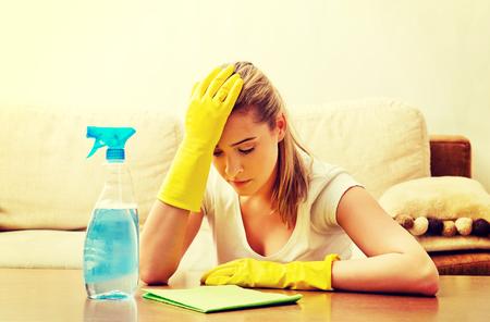 Table de nettoyage de jeune femme fatiguée dans des gants jaunes