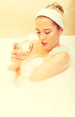 Woman relaxing in bath with glass of champagne Foto de archivo - 113301268