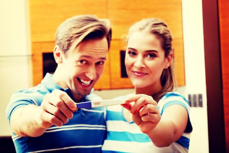 Young happy couple with pregnancy test standing in kitchen