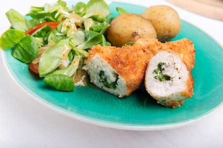 Kiev cutlet with jacket potatoes and salad.