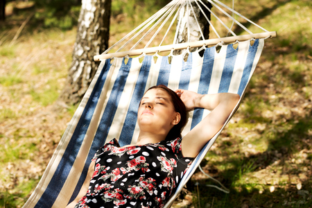 Young woman lying in a hammock under trees in sunny summer day. Stock Photo