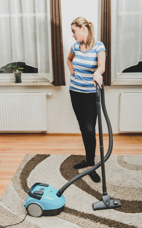 Woman vacuuming in home Stock Photo