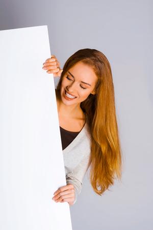 Woman holding a white blank board Standard-Bild - 127485410