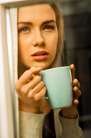 Woman with cup of coffee in window Standard-Bild - 127485430