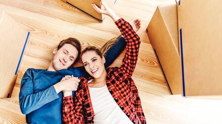 Smiling couple lying on floor Standard-Bild - 128568267
