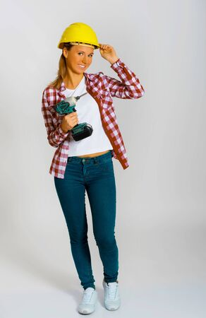 Builder woman with drill Imagens