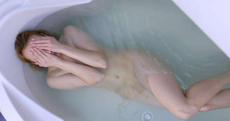 Relaxed woman lying in bath washing her hair.