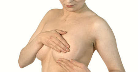 Close-up of young shirtless woman examining her breasts.