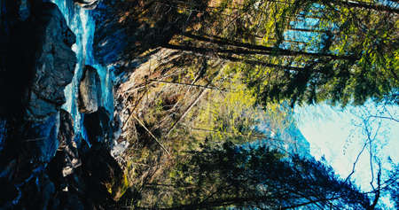 A river flows over rocks in this beautiful scene in the Alps mountains in spring. Vertical 4k 版權商用圖片