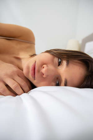 Sad woman is lying in bed