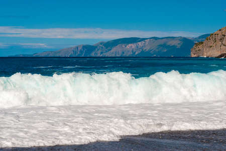 foamy: Foamy wave breaking on the shore in a beach near Maratea southern Italy Stock Photo