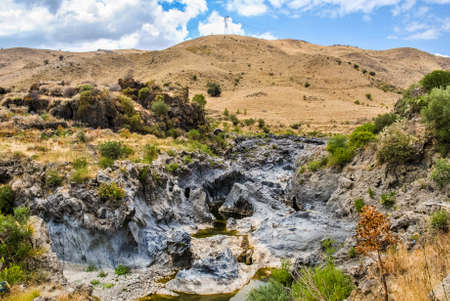 solidified: The river Simeto passes through an ancient solidified lava flow of volcano Etna Stock Photo