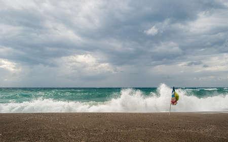 mare agitato: Solitario ombrellone sulla spiaggia durante una tempesta di vento con mare mosso sullo sfondo