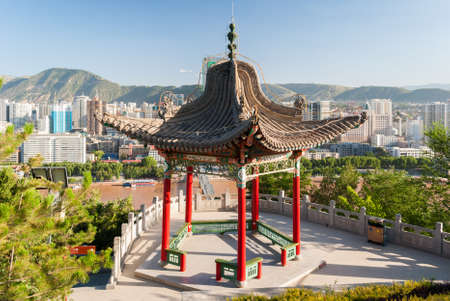 Pavilion in the Baitashan Park in Lanzhou, with skyline of the city in background Imagens