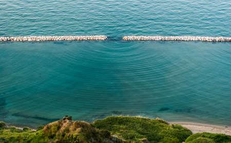 Des ondes de diffraction dans la mer voient le long du littoral près de Pesaro