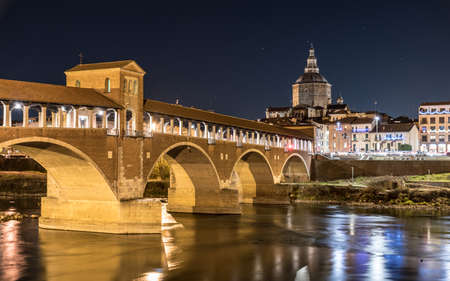 Night view of Pavia with Ponte Coperto and the river Ticino