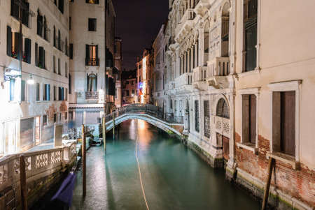 Night view of a typical canal in Venice with the light trail of a boat