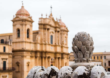 Baroque ornament in Noto (Sicily, Italy); in the background blurred view of the cathedral