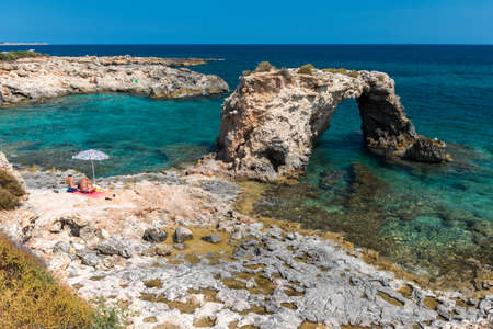 Rocky coastline with a natural arch at punta Asparano, near Siracusa