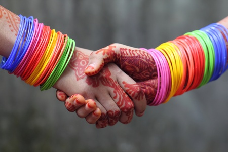 indian bride: Shaking hands decorated with colorful bracelets and henna tattoo in Indian subcontinent Stock Photo