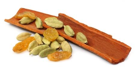'cinnamon bark':  Cinnamon bark with cardamom seeds and raisin