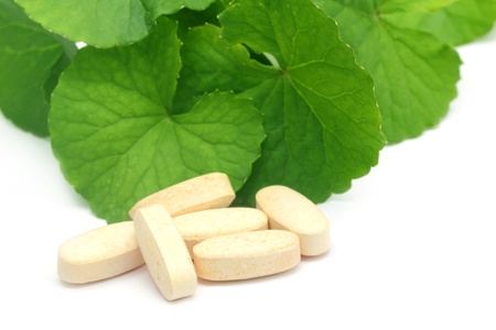 Medicinal thankuni leaves with pills photo