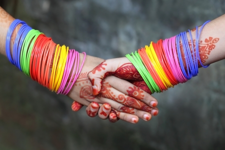 23296978 shaking hands decorated with colorful bracelets and henna tattoo - Bangles