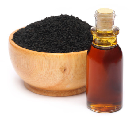 Nigella sativa or Black cumin with essential oil over white photo