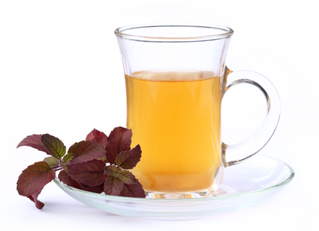 Cup of herbal tea with red tulsi leaves over white background photo