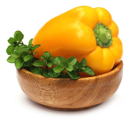Yellow capsicum with mint leaves on a bowl photo
