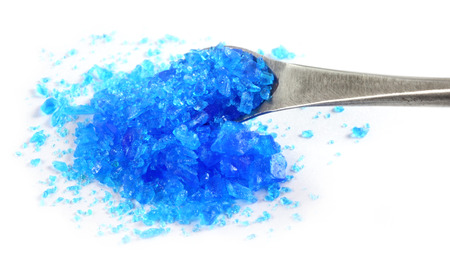 Copper sulphate with a steel spatula over white background photo