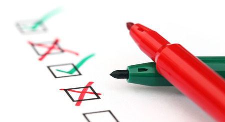 cheque en blanco: Revise la lista con dos plumas sobre papel blanco