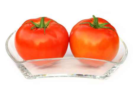 Two ripe tomatoes on a transparent bowl over white background photo