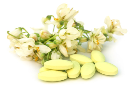 Moringa flower with pills over white background photo