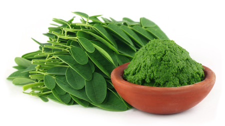 Moringa leaves with paste on a brown bowl photo