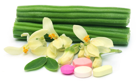 Moringa pills with flower and leaves over white background photo