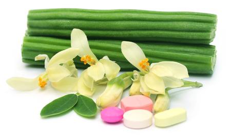 benzolive: Pillole Moringa con fiori e foglie su sfondo bianco Archivio Fotografico