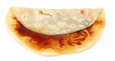 atta: Handmade roti bread with molasses over white background