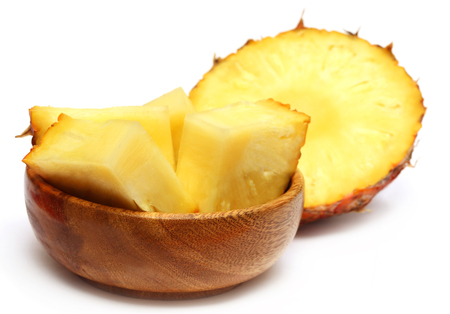 Sliced pineapple on a wooden bowl over white background photo