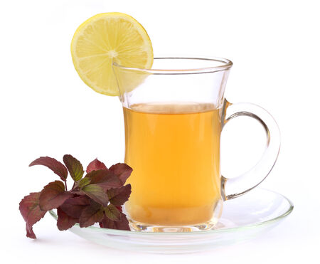 Cup of herbal tea with red tulsi leaves and lemon over white background photo