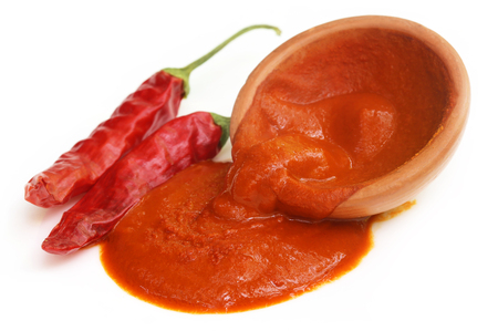 Red hot chilies with paste over white background photo