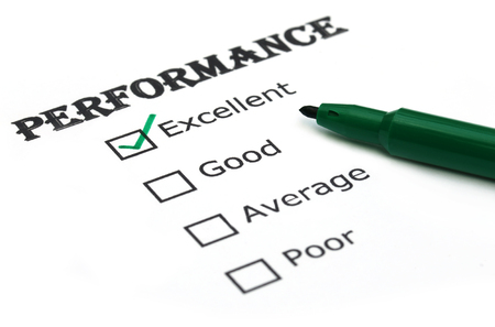 evaluating: Evaluating performance with a green pen Stock Photo