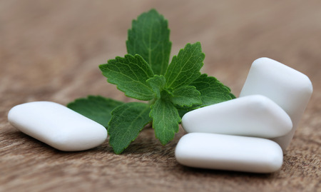 steviol: Chewing gum with green stevia on wooden surface
