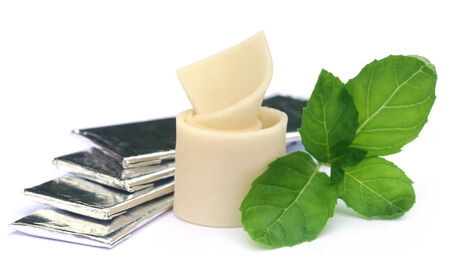 chew over: Chewing gum with mint leaves over white  background