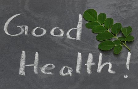marango: Moringa leaves with Good Health written in a slate by whtie chalk