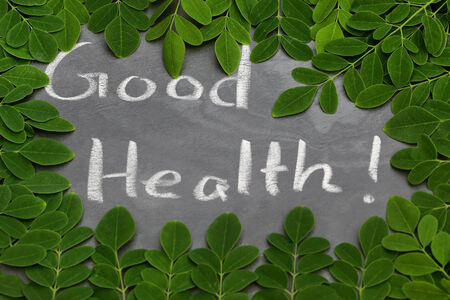 sonjna: Moringa leaves with Good Health written in a slate by whtie chalk
